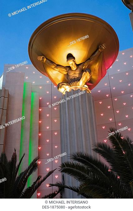 Las Vegas, Nevada, United States Of America, An Illuminated Male Figure Holding A Gold Bowl At Night