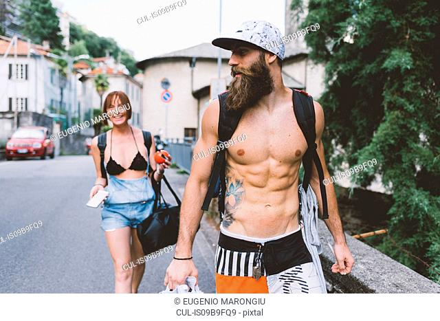 Young couple in swimwear and backpacks strolling in Como, Lombardy, Italy