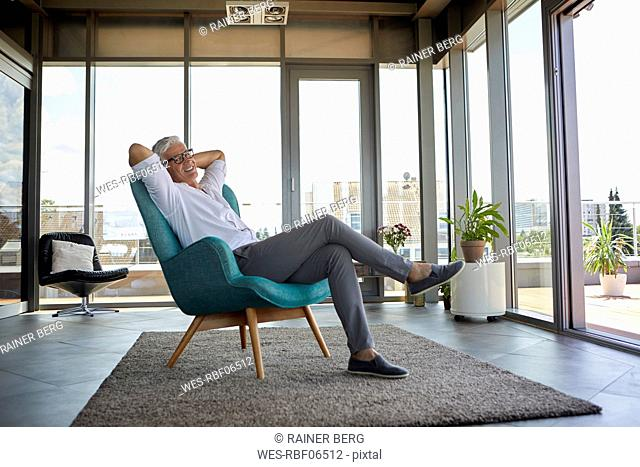 Smiling mature man relaxing in armchair at the window at home