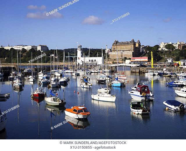 Boats in the harbour and the lighthouse from East Pier at Scarborough North Yorkshire England