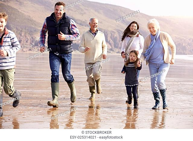 Multi Generation Family Running On Winter Beach