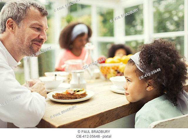 Multi-ethnic father and daughter playing staring game at kitchen table