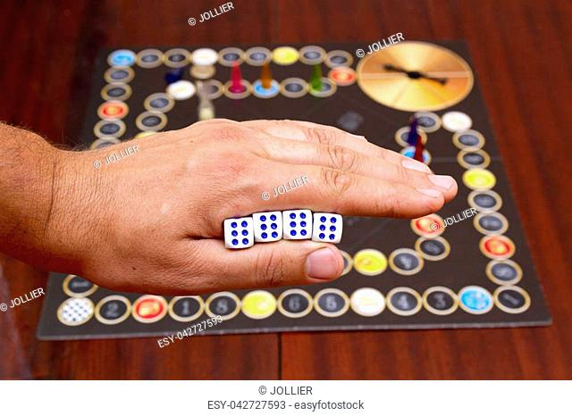 Man's hand holds the cubes against the background of the playing field