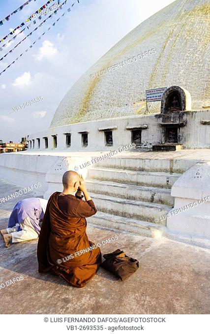 Western nun praying at Bodhnath stupa. Kathmandu, Nepal