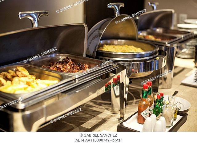 Prepared food in warming dishes on buffet