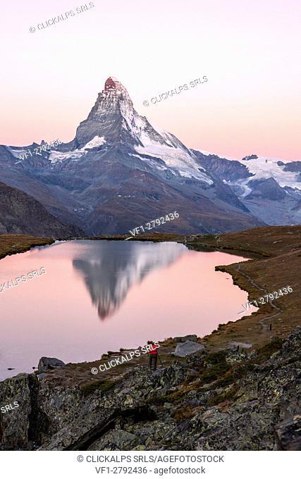 The photographer captures the Matterhorn under a pink sky at dawn from Stellisee. Zermatt Canton of Valais Pennine Alps Switzerland Europe