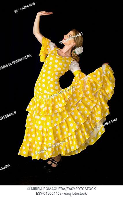 Flamenco dancer dressed in yellow posing