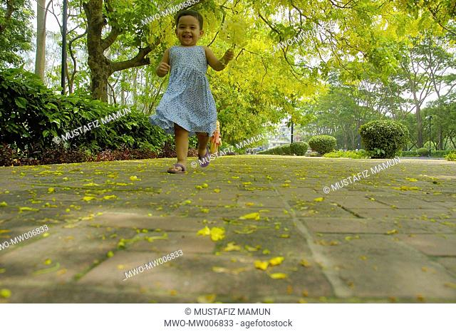 A little girl runs under Sonalu or Golden shower tree at Jatiya Sangsad Bhaban premises in Dhaka Dhaka, Bangladesh May 17, 2007