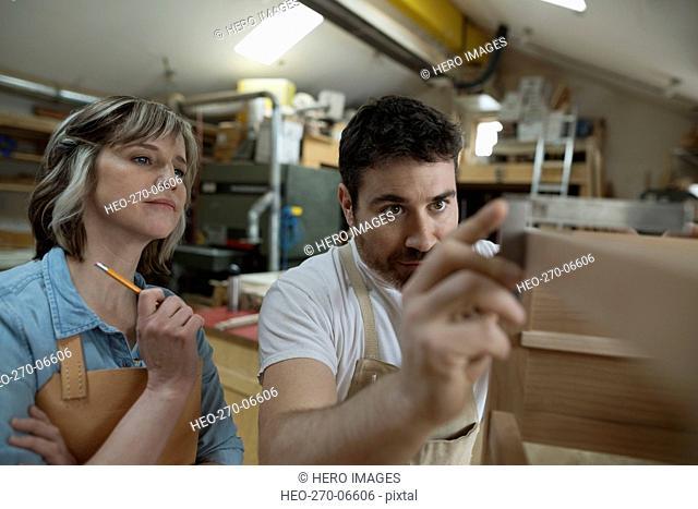 Carpenters measuring furniture in workshop