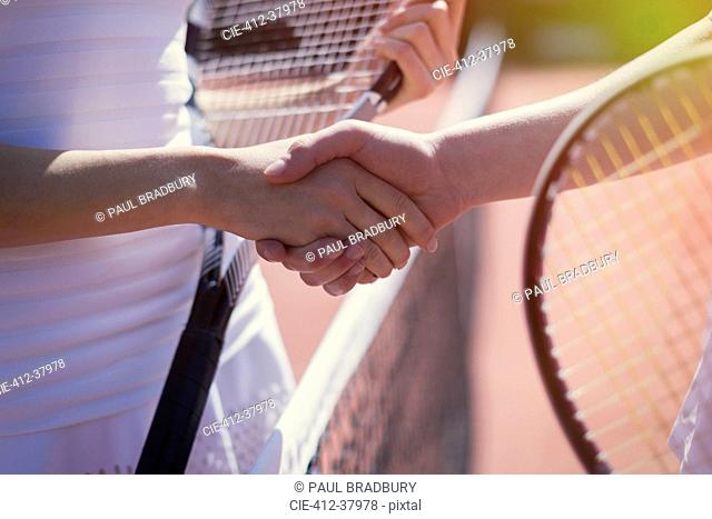 Close up tennis players handshaking in sportsmanship at net