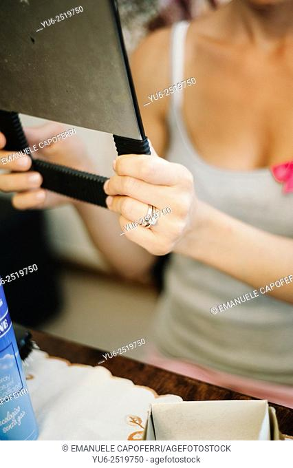 Woman holds a mirror in the hands while it is being rigged
