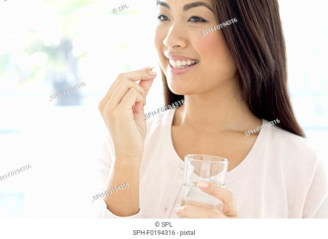 Woman holding pill and glass of water