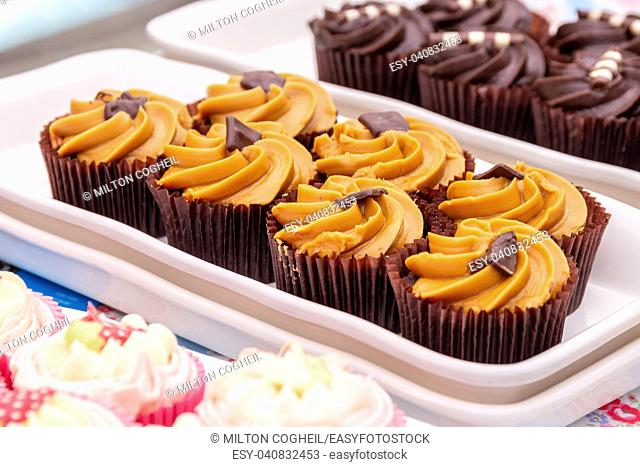 Homemade orange and chocolate cupcakes on a market stall