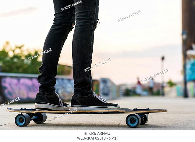 Close-up of young woman riding skateboard