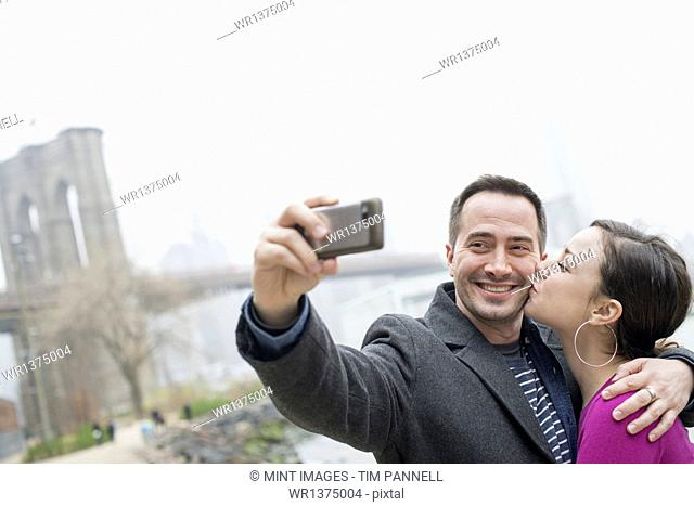 New York city. The Brooklyn Bridge crossing over the East River. A couple taking a picture with a phone, a selfy of themselves