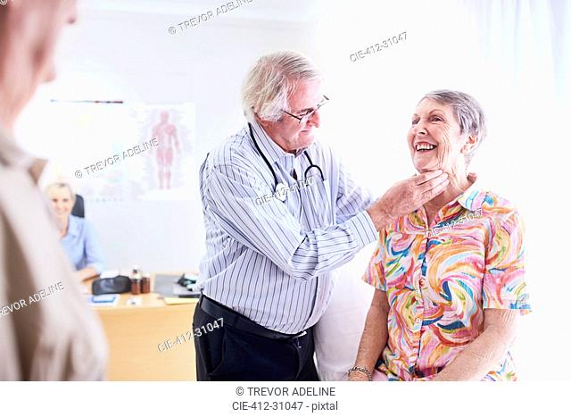 Doctor checking senior woman's glands at checkup