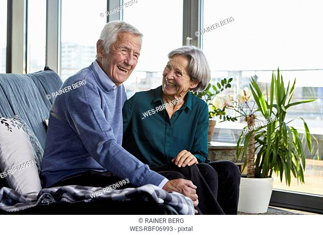 Laughing senior couple sitting together on couch