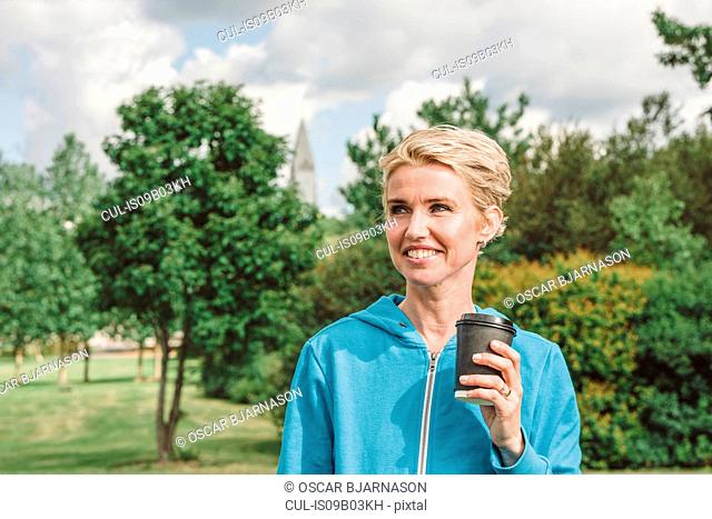 Female runner with takeaway coffee in park, Reykjavik, Iceland