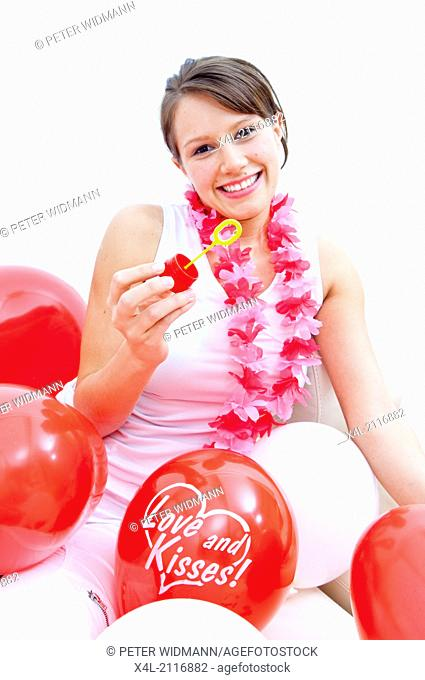 Young woman with flower necklace, soap bubbles and balloons (model-released)