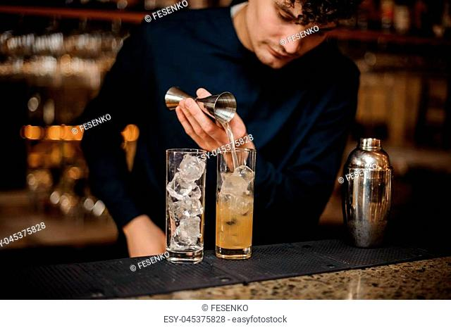 bartender with curly hair and in a blue shirt begins preparing two alcoholic cocktails, pouring alcohol on ice
