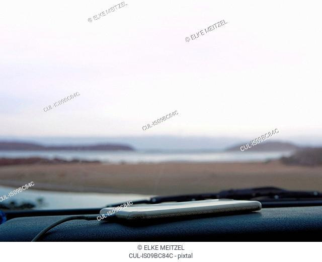 Smartphone on car dashboard, coastal view seen through car windscreen, Broulee, New South Wales, Australia