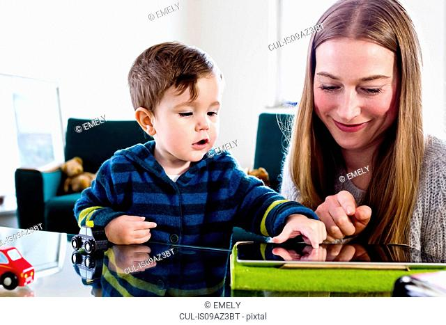 Mid adult woman and baby son using touchscreen on digital tablet at table