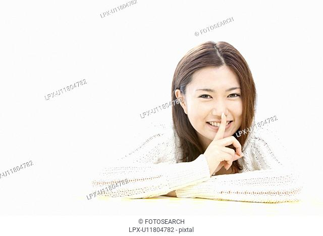 Young woman with finger on lips, Tokyo Prefecture, Honshu, Japan