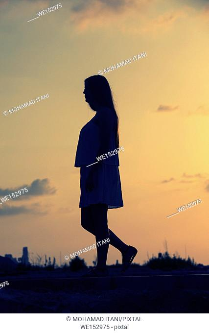 Full length silhouette of a woman walking outdoors at sunset