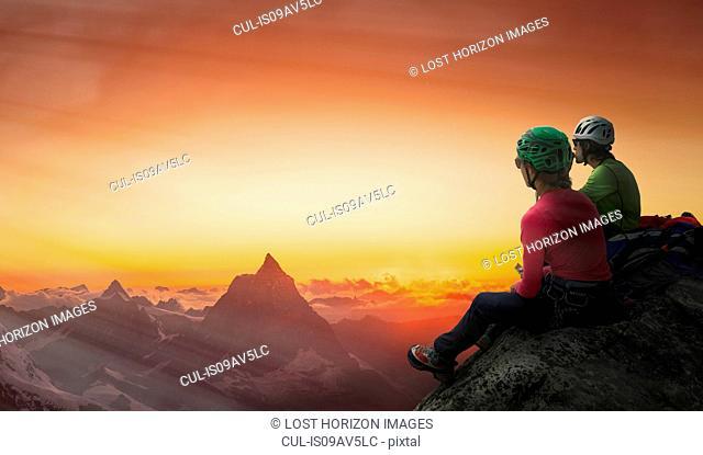 Climbers on mountain top watching sunset over Matterhorn, Mont Blanc, France