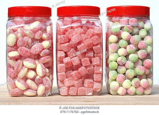 jars containers of traditional british sweets candies including rhubarb and custard cola cubes and rosey apples in the uk
