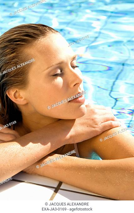 Woman with eyes closed leaning on edge of swimming pool