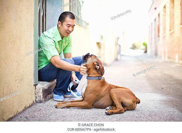Mid adult man petting his boxer dog on doorstep
