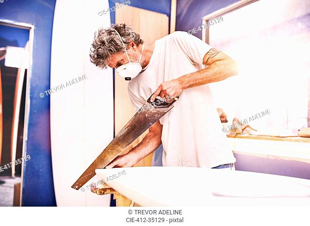 Male surfboard designer wearing protective mask and using saw in workshop