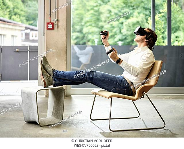 Man wearing VR glasses sitting on chair