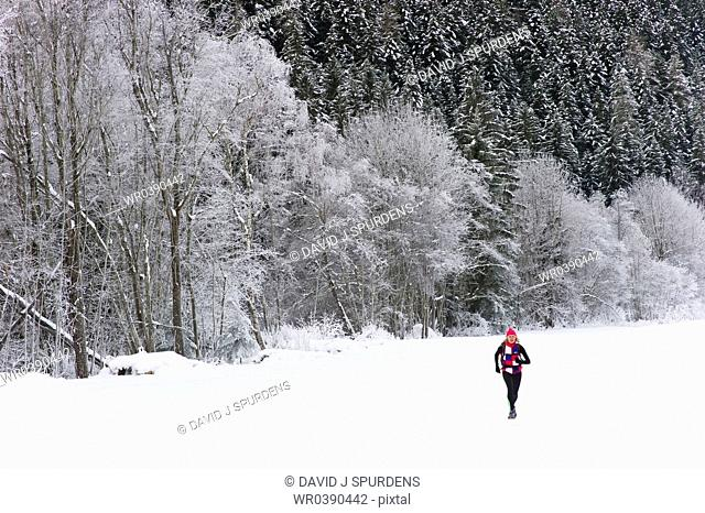 A jogger runs on snow field past snow covered forest
