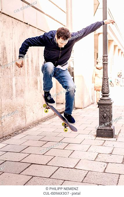 Mature man doing mid air skateboarding trick on city sidewalk