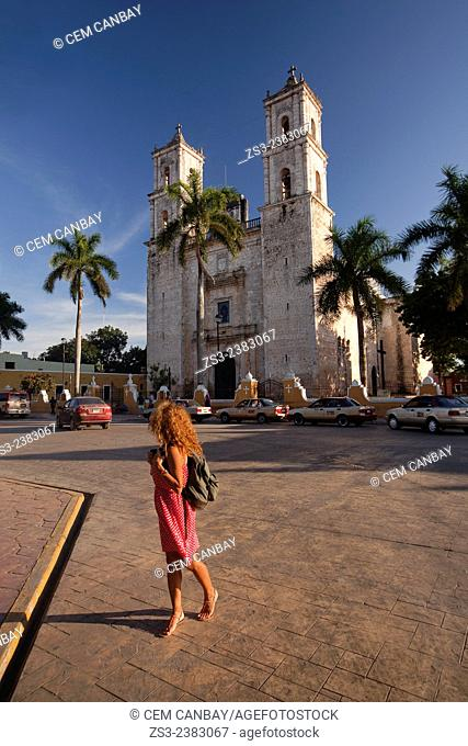 Tourist woman crossing the street near the San Gervasio Cathedral with the vehicles in the background, Valladolid, Yucatan Province, Mexico, Central America