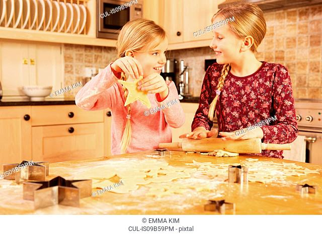 Two girls baking star shape pastry at kitchen table
