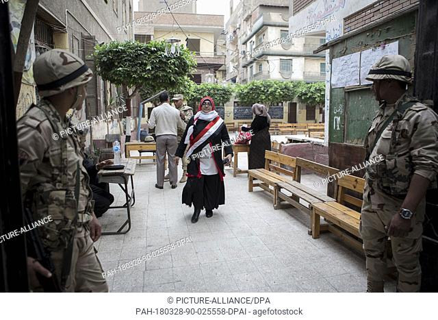 dpatop - An Egyptian woman wrapped in an Egyptian flag-inspired sash exits a polling station after voting on the 3rd day of the 2018 Egyptian presidential...
