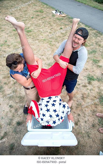 Two young men dunking friend into cooler on Independence Day, USA