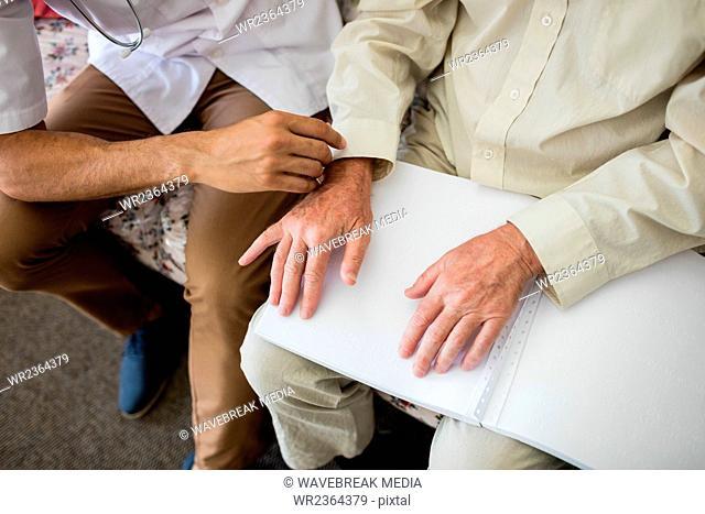 Blind senior man using braille to read