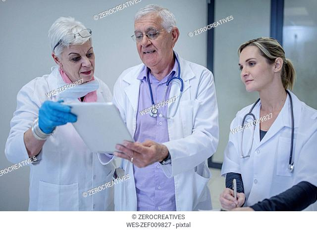 Three doctors with digital tablet discussing