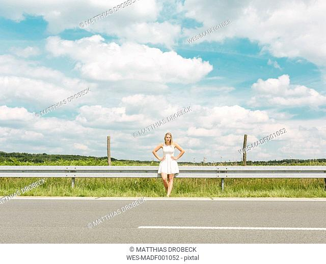 Young woman in white dress standing at the roadside