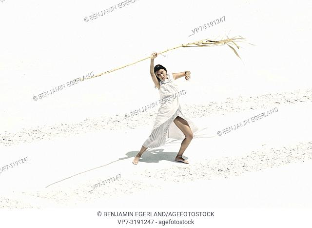 Woman with dry bamboo stick in desert, dancing