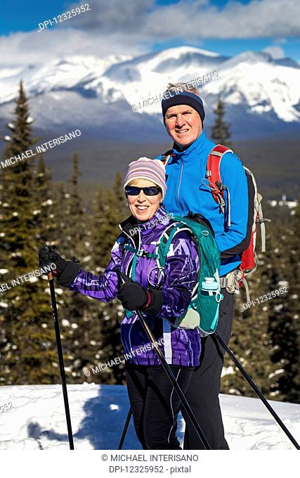Male and female cross country skiiers on a lookout with snow covered mountains, blue sky and clouds in the background; Lake Louise, Alberta, Canada