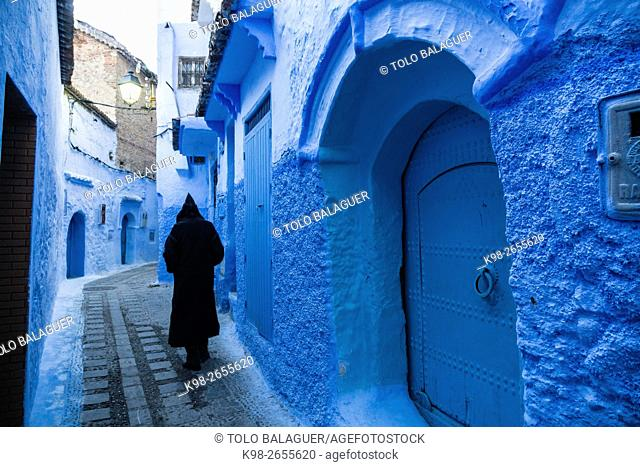 Morocco, Chefchaouen, Rear view of hooded man walking in medina