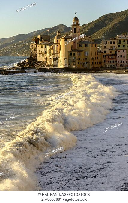 rough sea with wave shuttering in front of Assunta church apse and Dragonara castle jin picturesque village , shot on a sunny bright winter day, Camogli, Italy