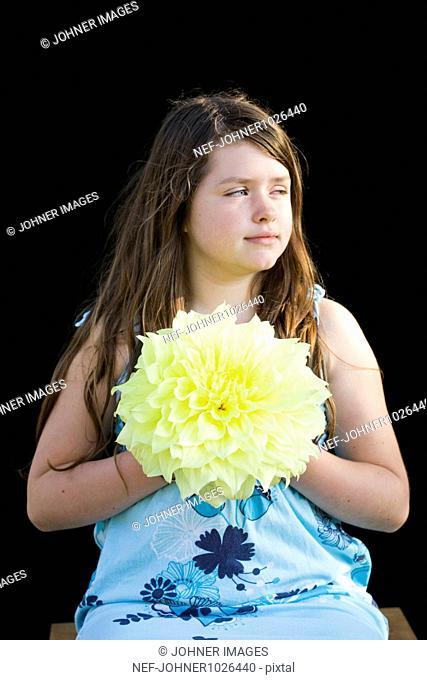 Sweden, Uppsala, girl (10-11) holding dahlia flower head