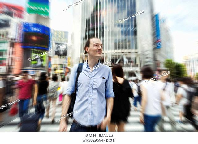 A young Caucasian man with a backpack on a crowded street in downtown Tokyo