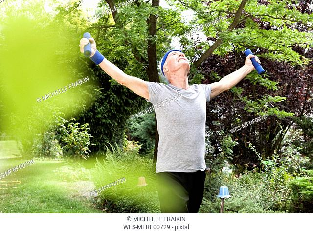 Senior man doing fitness training with dumbells in garden